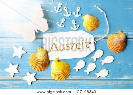 Flat Lay View Of Label With German Text Auszeit Means Downtime. Sunny Summer Greeting Card. Butterfly, Shells And Fishes On Blue Wooden Background