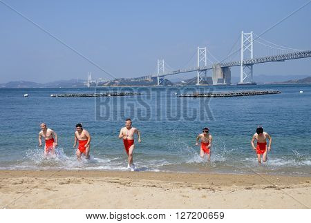 KAGAWA, JAPAN - APR 19: Traditional scene of Japanese nudity men bathe in holy sea water at April 17, 2016, in Nakanda-beach, Kagawa Japan.