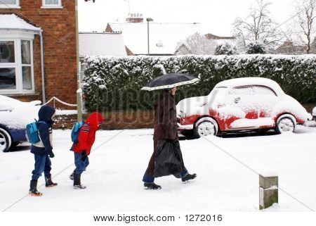 Woman And Children Walking In The Snow