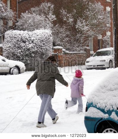Woman And Girl Walking In The Snow