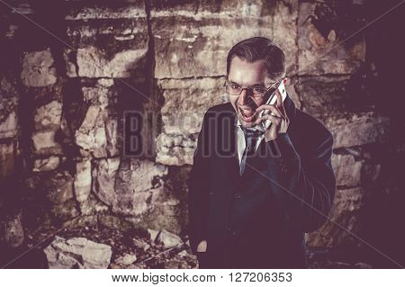 Surprised businessman is talking by phone on the night rocks background.
