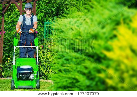 Caucasian Gardener Mowing the Grass Using Professional Grass Mower. Garden Works.
