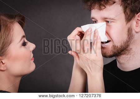 Hygiene and skincare concept. Protection and help in relationship. Smiling happy woman wipe cream face nose of funny man by hygienic tissue. Girlfriend takes care of her boyfriend.