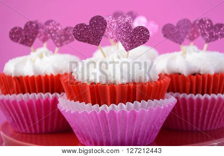 Pink And White Cupcakes With Heart Shape Toppers.