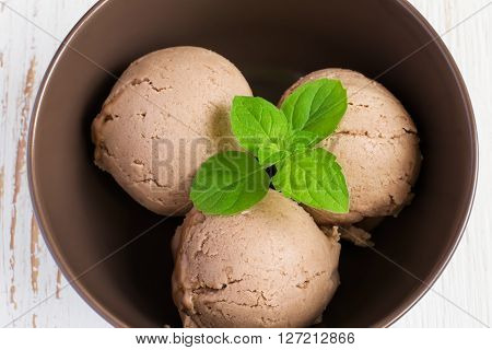Chocolate ice cream with mint leaf in brown bowl top view.