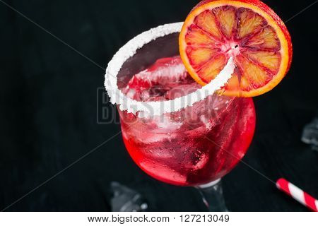 Glass with a cocktail decorated with a border and orange.