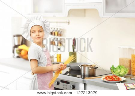 Little girl cooking spaghetti on the kitchen.
