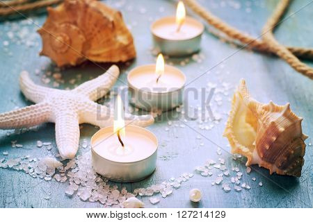 Candles seashells and starfish on vintage background tinted.