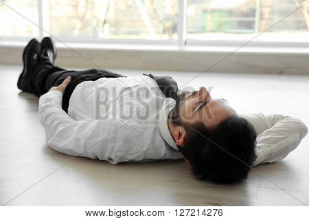 Young handsome businessman lying on the floor