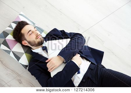 Young tired businessman with a laptop sleeping on the floor
