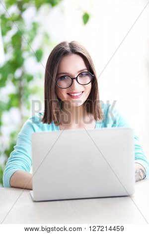 Woman sitting at the table and working with laptop