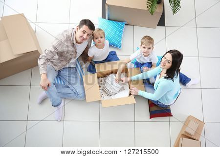 Moving concept. Happy family unpacking boxes in new house, top view