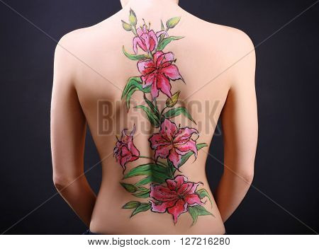 Flower body art on female back over black background