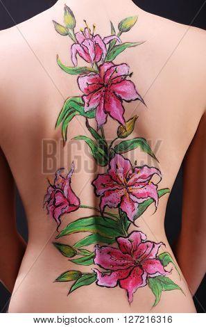 Flower body art on female back over black background
