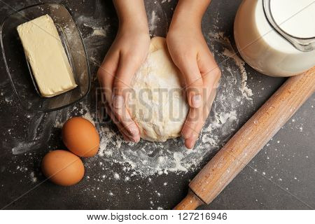 Female hands holding dough, top view