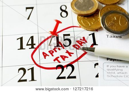 April tax day written and pinned in a calender, close up