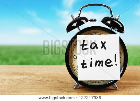 Tax concept. White sticker with Tax time on alarm clock on table