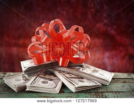 Pile of dollars with bow as gift on red background