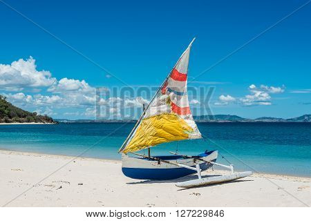 Malagasy outrigger pirogue with colorful makeshift sails on the white beach
