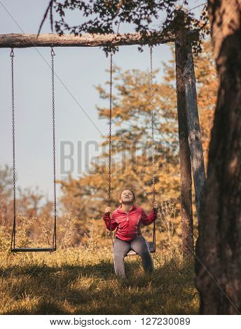 Little girl in swing on tree