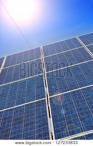 Solar panel with bright sun on a blue summer sky