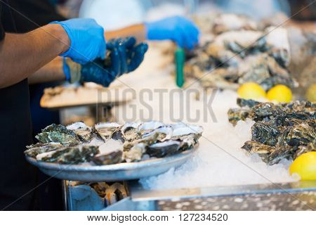 close-up of shucking fresh oysters and arranging them on the plate in restaurant