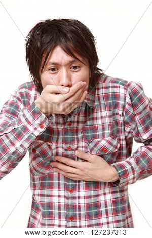 young Japanese man feels like vomiting on white background