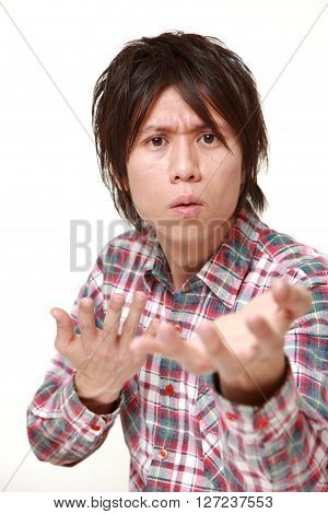 portrait of young Japanese man requests something on white background