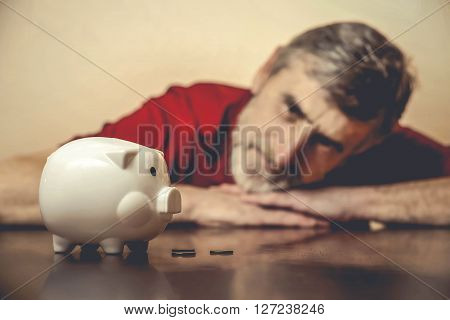 Senior man looking at piggy bank - vintage color correction