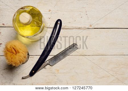 A sharp straight razor brush and cologne aftershave on wooden background