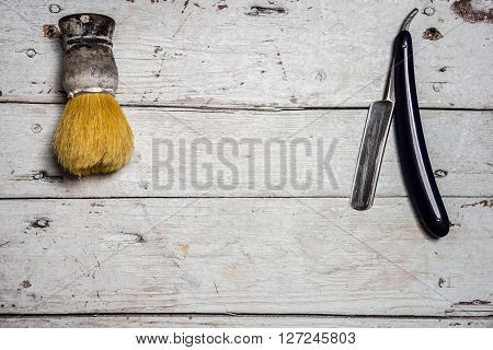 Straight Razor and shaving supplies on wooden background