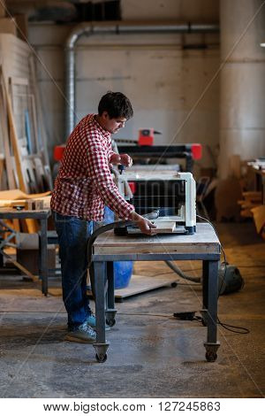 Carpenter working with a wooden board on edging planers woodworking shop workshop tools