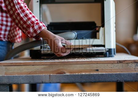 Carpenter working with a wooden board on edging planers woodworking shop workshop tools close-up ** Note: Shallow depth of field