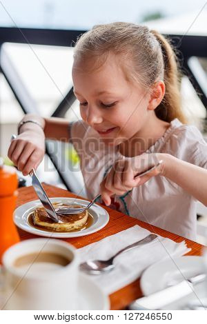 Adorable little girl eating pancake for breakfast in restaurant