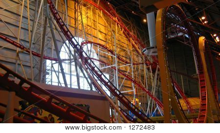 an indoor rollercoaster with a double loop poster