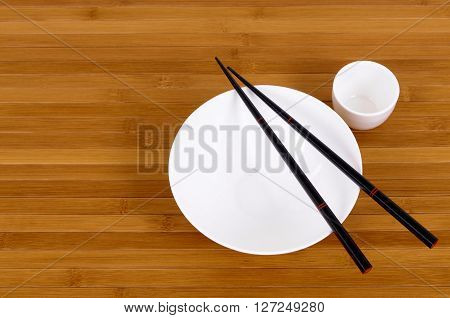 White empty rice bowl and sake cup with black chopsticks on a bamboo background.