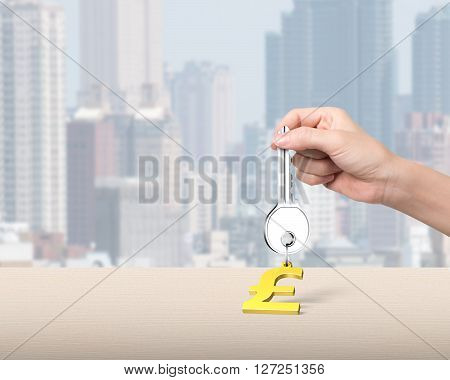 Woman hand holding silver key with golden dollar sign shape keyring on table and city skyscraper background, 3D illustration.