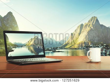 notebook and cup on table, Lofoten islands, Norway as background
