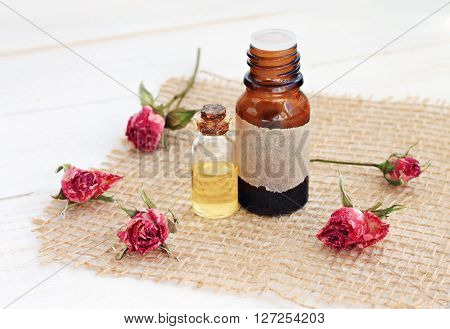 Rose essential oils. Bottles of oil, dried rosebuds. Floral aromatherapy scent and skincare.