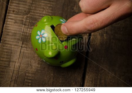 Male hand with a coin and a piggy bank on wood saving money concept