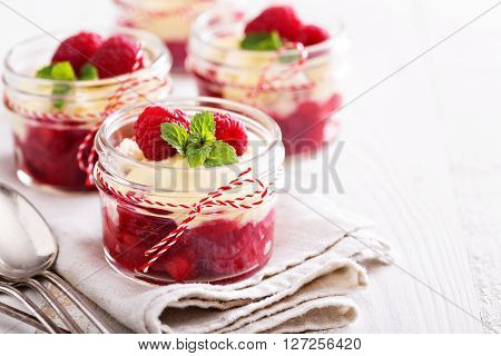 Berry crumble dessert with cream sauce in small jars