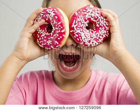 Studio portrait of a beautiful little girl looking through a donut