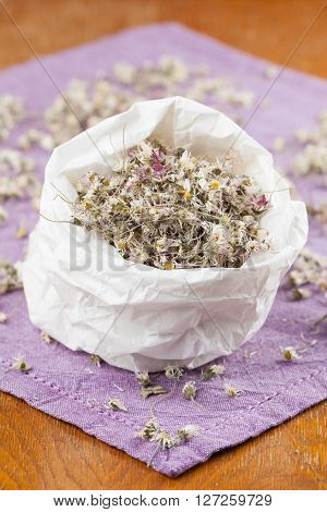 Paper bag with dry daisy flowers for herbal tea