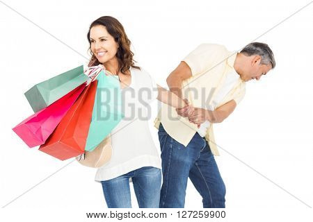 Smiling wife holding shopping bags with husband pulling her hand while standing on white background