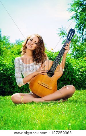 Romantic pretty girl sitting on a lawn with her guitar. Summer.