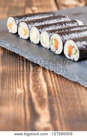 Homemade maki sushi rolls on a slate board