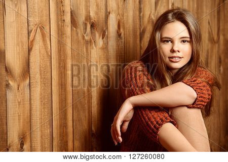 Pretty smiling teen girl in a sweater sitting by a wooden wall. Modern teen generation. Youth fashion. Healthy hair, haircare.