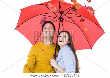 Happy couple under an umbrella throwing leaves on white background