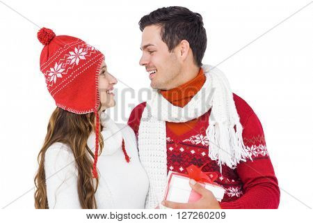 Happy couple with winter clothes holding gift box on white backgrond