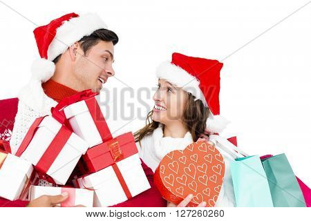 Happy couple with santa hats holding gift boxes and shopping bags on white background